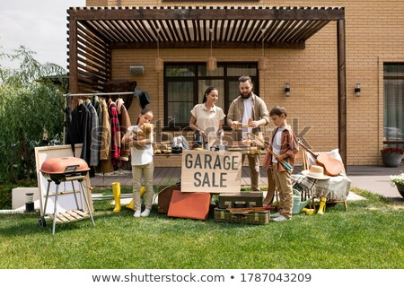 Smiling man standing in front of a shop grille Stock photo © photography33