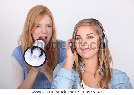 Young girl oblivious to her friend yelling into a megaphone Stock photo © photography33