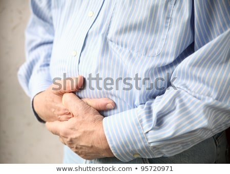 businessman holding his stomach in pain or indigestion stock photo © dacasdo