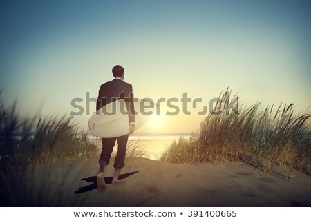 Business man in suit walking with surfboard on the beach stock photo © epstock
