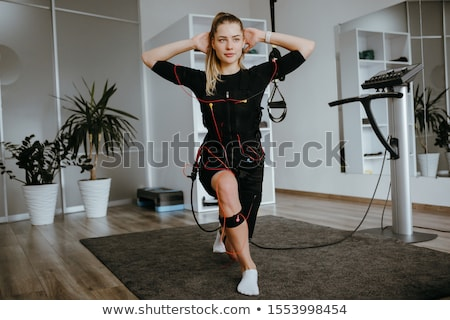 Young woman doing exercise  in Electro Muscular Stimulation EMS training costume  Stock photo © Nejron
