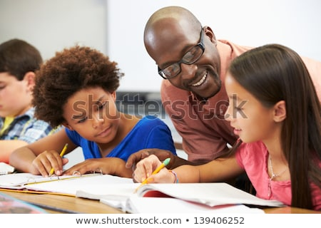 teacher helping male pupil studying at desk in classroom stock photo © monkey_business