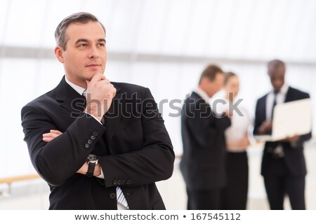 Elegant business man holding his hand to his chin Stock photo © feedough