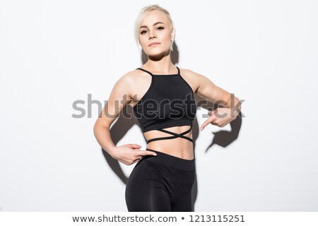 fitness woman showing finger at her belly stock photo © deandrobot