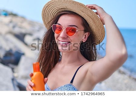Stock photo: happy young woman in swimsuit holding sunscreen