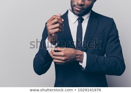 Elegáns fiatalember megjavít kabátujj oldalnézet néz Stock fotó © feedough