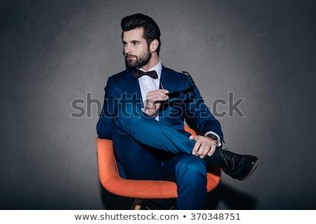 Elegáns férfi ül stúdió lábak keresztbe néz Stock fotó © feedough