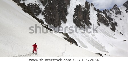 Panoramic view on snowy sunlit mountains and cloudy sky Stock photo © BSANI