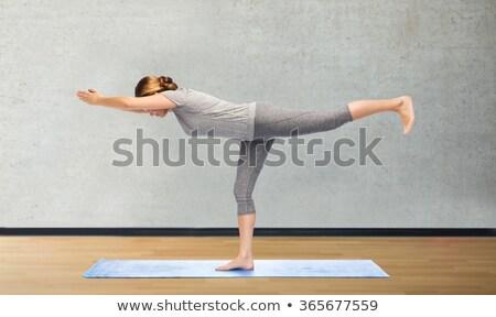 woman making yoga warrior pose on mat stock photo © dolgachov