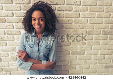 Mulher em pé parede de tijolos bela mulher cabelos longos moda Foto stock © deandrobot