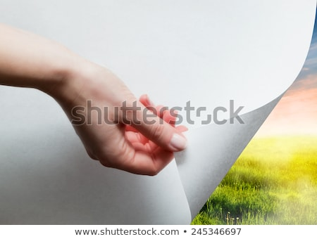 Hand pulling edge of a paper to uncover, reveal green landscape Stock photo © photocreo