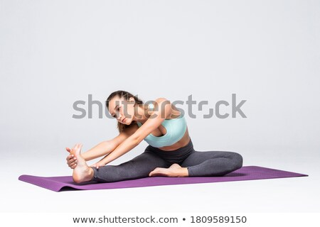 Full length of beautiful young sportswoman standing and stretching legs Stock photo © deandrobot