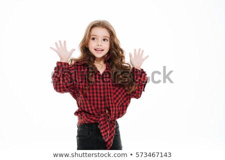 Sorridente little girl camisas em pé as mãos levantadas Foto stock © deandrobot