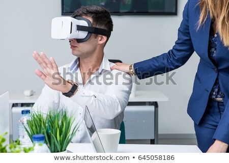 Confused young man wearing virtual reality device Stock photo © deandrobot