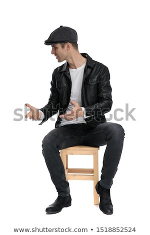 man in leather jacket looks to side while sitting stock photo © feedough