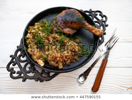 Chicken grilling with a side dish of buckwheat, on a black metal Stock photo © Yatsenko