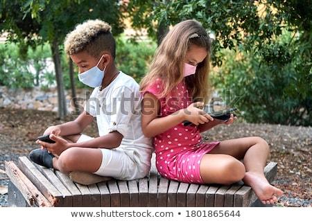 два мальчики сидят скамейке играет таблетка Сток-фото © courtyardpix
