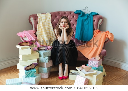 portrait of a tired exhausted girl in dress sitting on a sofa stock photo © deandrobot