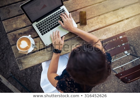 Top view of young brunette woman sitting by the table Stock photo © deandrobot