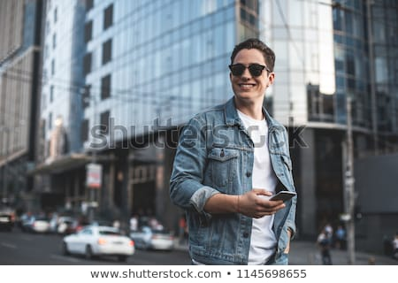 smiling smart casual man holding his sunglasses looks to side stock photo © feedough