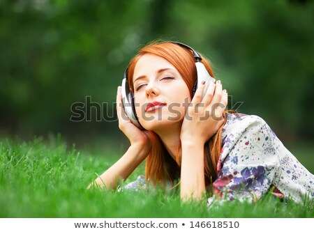 redhead girl listening music at green grass stock photo © massonforstock