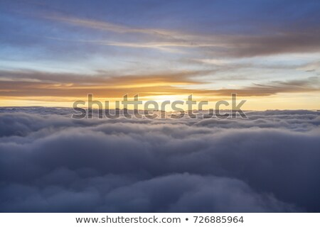 Stock photo: Aircraft flight over the clouds during sunrise