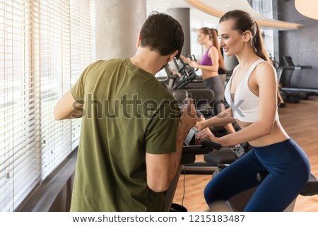 Personal trainer setting the timer of the stationary bicycle for his client Stock photo © Kzenon