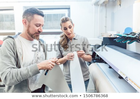 man and woman discussing a large format print stock photo © kzenon