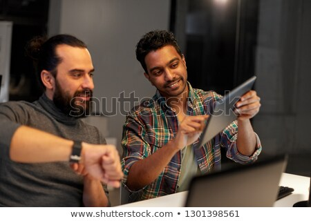 man with smartwatch and tablet pc at night office stock photo © dolgachov