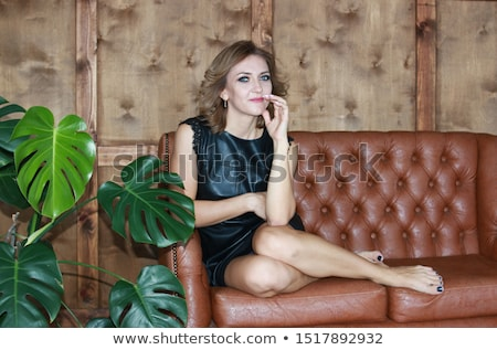 Gorgeous blonde woman in bright black dress on couch. Stock photo © studiolucky