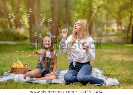 two young children blowing bubbles on countryside picnic stock photo © monkey_business