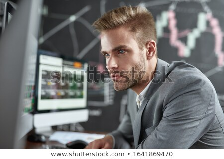Successful financial analyst sitting by desk in front of computer screen Stock photo © pressmaster