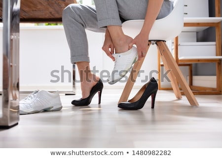 Woman Removes Black Shoes And Wear White Sneakers Stock photo © AndreyPopov