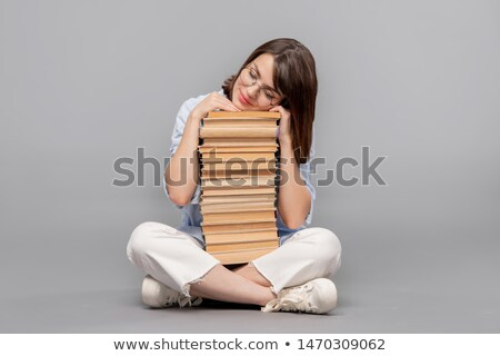 Clever female stuudent with crossed legs keeping her head on top of books Stock photo © pressmaster