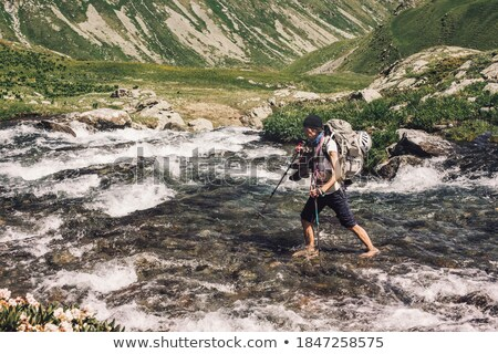 Young man with backpack crosses a mountain stream on a sunny day Stock photo © boggy