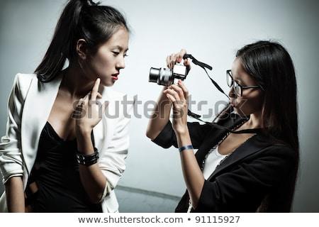 Attractive girl shoots by photocamera Stock photo © Aikon