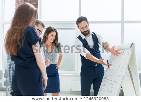 the man in the office is standing near the table and explains the schedule drawn on the magnetic boa stock photo © traimak