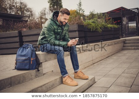 Smiling man dressed in coat sitting at the city street Stock photo © deandrobot