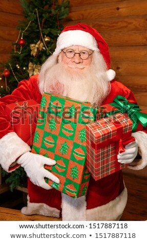 Happy Santa with four packed giftboxes standing in front of camera Stock photo © pressmaster