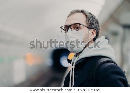 Serious man wears medical mask against transmissible disease, travels in subway, being in danger at  Stock photo © vkstudio