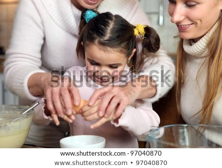 Little girl and her grandmother cracking an egg Stock photo © photography33
