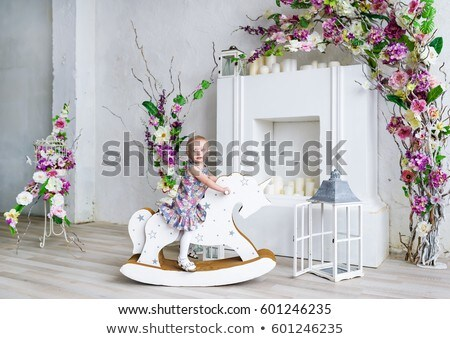 A little girl rides on a swing decorated with flowers in the home garden Stock photo © ElenaBatkova