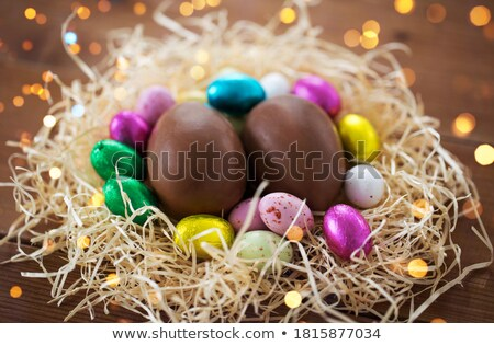 chocolate eggs in foil wrappers in straw nest Stock photo © dolgachov