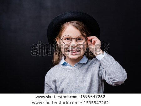Pretty little girl looking at you with toothy smile while touching eyeglasses Stock photo © pressmaster