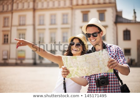 happy couple of tourists with map and camera Stock photo © dolgachov