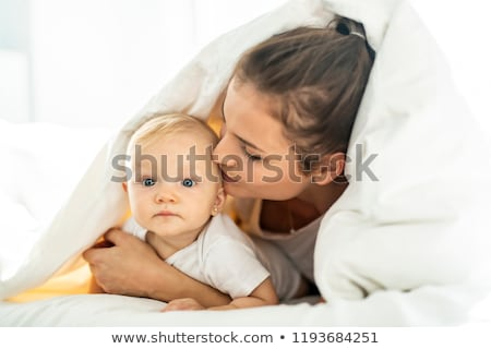 portrait of young mother with infant baby girl liying on the bed covered with a white blanket stock photo © lopolo