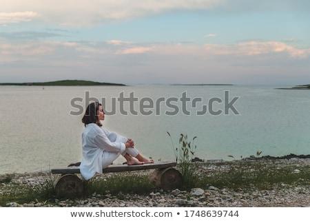 woman sitting on seashore Stock photo © OleksandrO