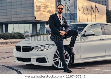 Handsome male with beard, dressed in formal suit, poses outdoor, has watch on arm, being in high spi Stock photo © vkstudio