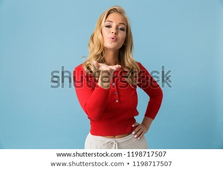 Portrait of flirting blond woman 20s wearing red shirt giving ai Stock photo © deandrobot
