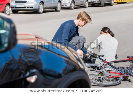 Helpful young man giving first aid to an injured woman after bicycle accident Stock photo © Kzenon